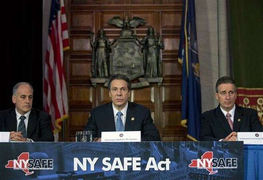 New York Gov. Andrew Cuomo, center, speaks during a news conference announcing an agreement with legislative leaders on New York's Secure Ammunition and Firearms Enforcement Act in the Red Room at the Capitol on Monday, Jan. 14, 2013, in Albany, N.Y. Also pictured are Secretary to the Governor Larry Schwartz, left, and Lt. Gov. Robert Duffy. (AP Photo/Mike Groll) Photo: AP / AP