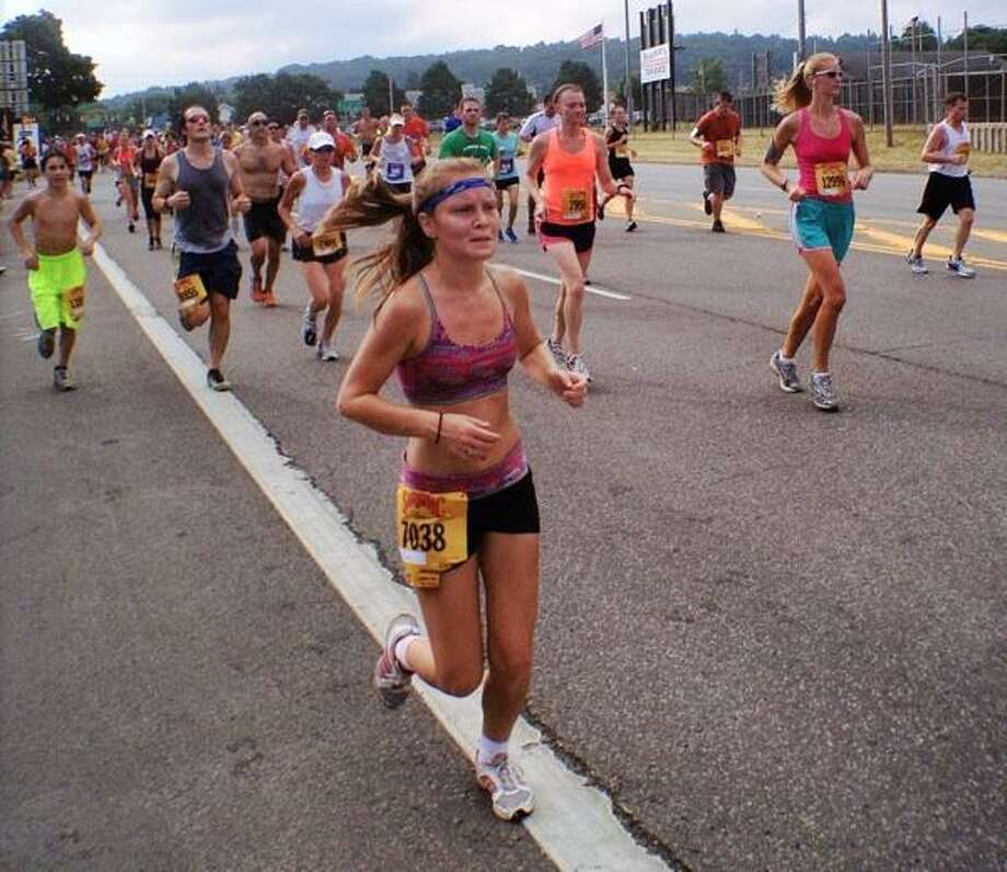 """Dispatch Staff Photo by JOHN HAEGER <a href=""""http://twitter.com/oneidaphoto"""">twitter.com/oneidaphoto</a> Runners pass the six mile mark during the Boiler Maker 15 K road race in July 2012 in Utica."""