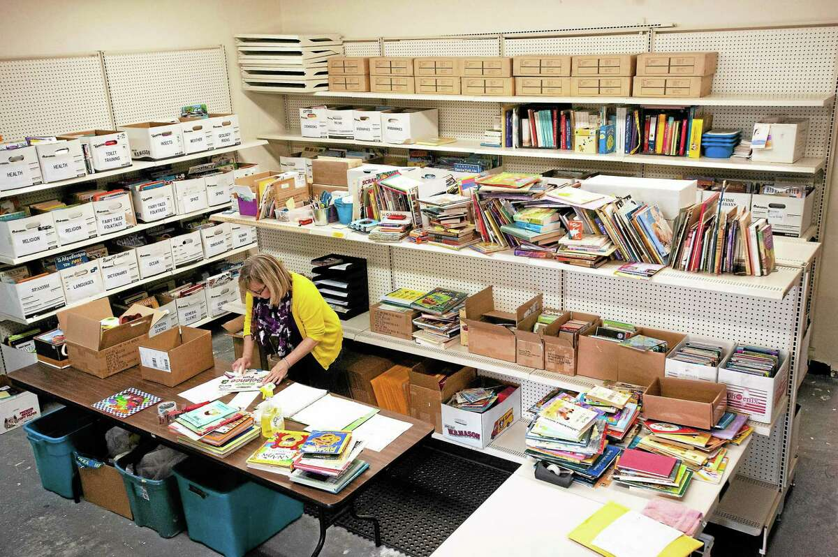 Linda Sylvester, Books for Kids coordinator, cleans incoming books at the Read to Grow office at 53 School House Road in Branford.
