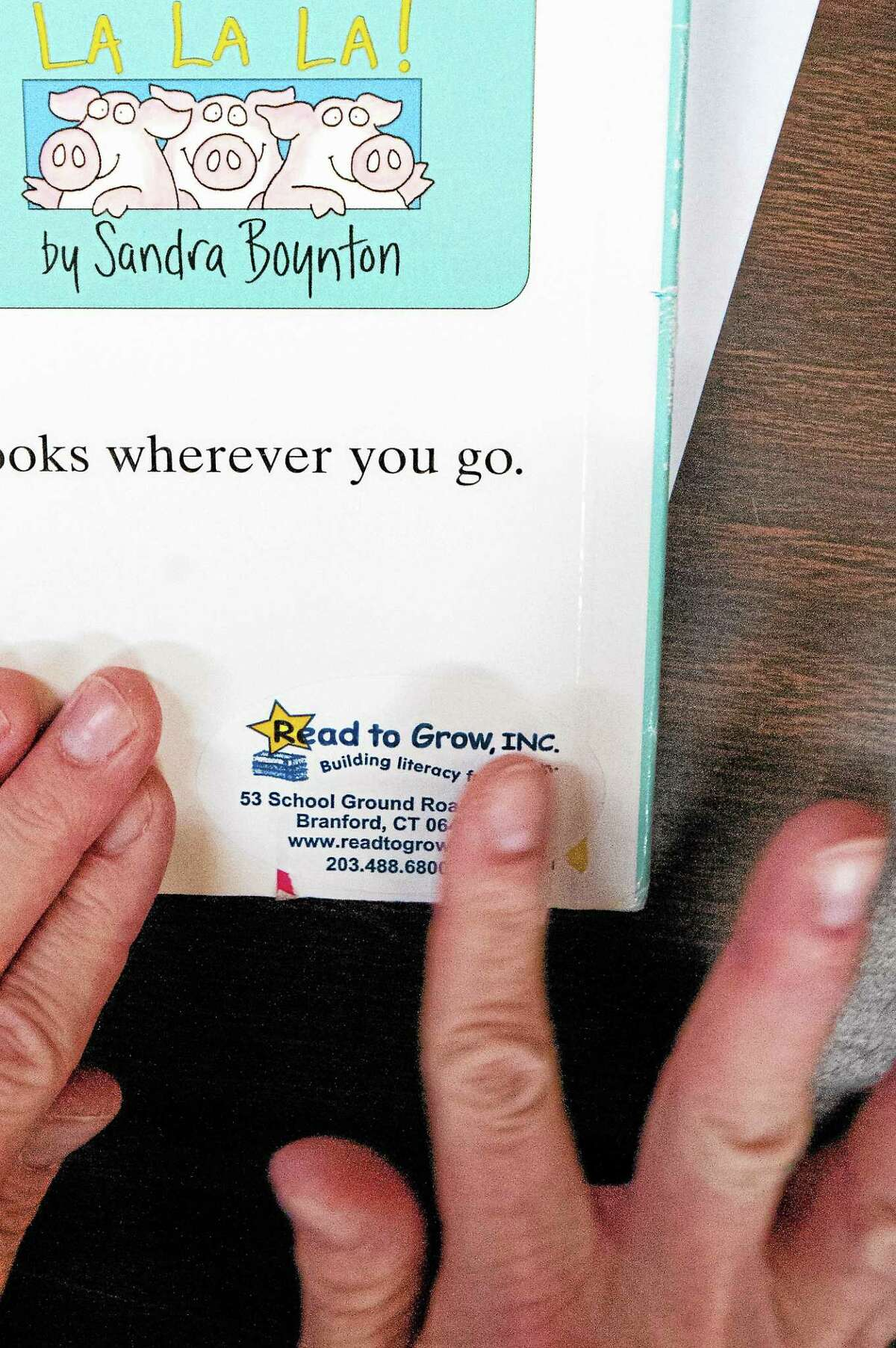 Linda Sylvester, Books for Kids coordinator, applies a sticker to a book ready to be distributed at the Read to Grow office at 53 School House Road in Branford.