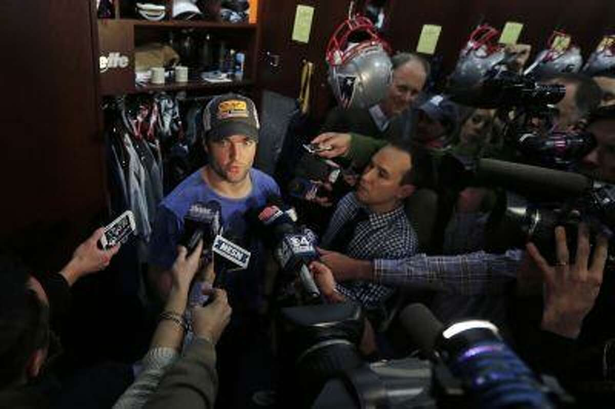 Wes Welker is surrounded by members of the media in the locker room after in Foxborough, Mass., Jan. 2, 2013.