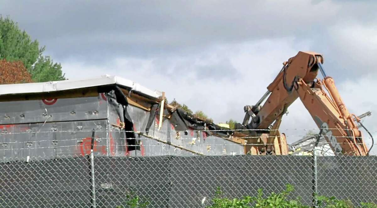 In this image taken from video, a backhoe rips into the roof of the Sandy Hook Elementary School in Newtown as demolition begins on the building.