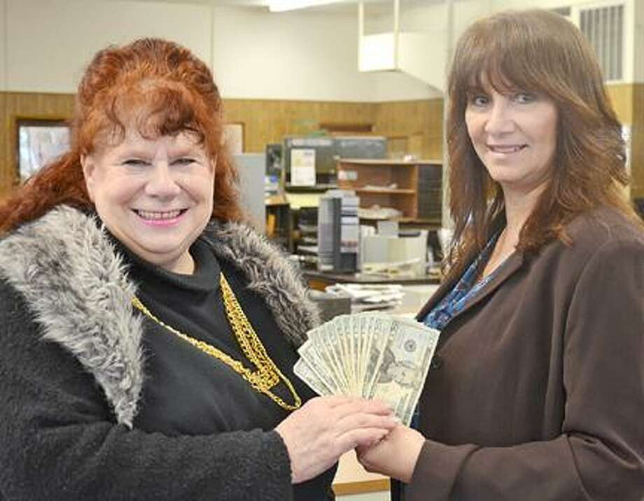 Dispatch Staff Photo by KURT WANFRIED Susan Golden, left, receives her winnings Tuesday from Karen Alvord, general manager and advertising director of Oneida Publications.