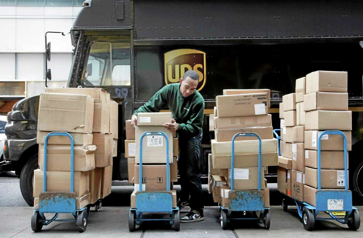 FILE - In this March 10, 2011, file photo, a United Parcel Service driver unloads packages from a truck and arranges them for delivery in New York. UPS will be hiring 55,000 U.S. seasonal workers to help with an increase in volume over the holiday season. The world's biggest package delivery company said Friday, Oct. 25, 2013, that it foresees peak season daily volume rising 8 percent this year. (AP Photo/Mark Lennihan, File)