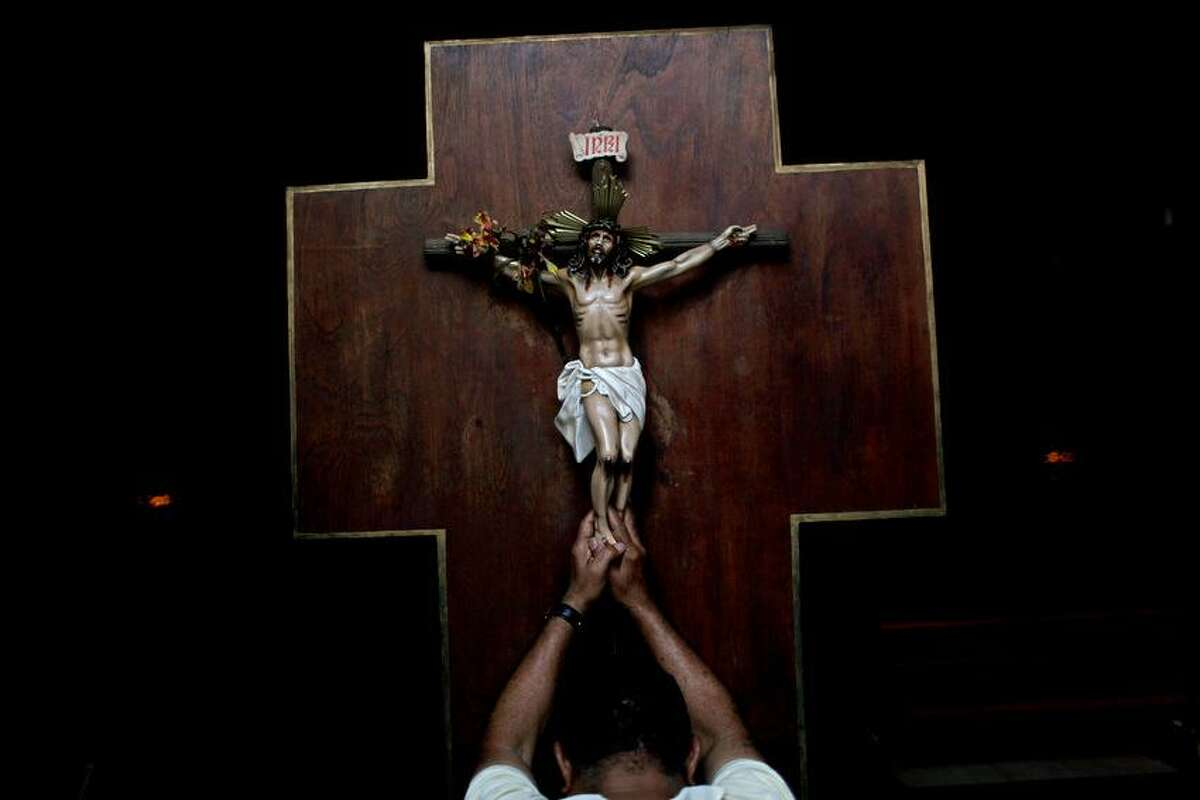 A man prays as he touches a crucifix at La Candelaria church in Caracas, Venezuela, Wednesday, March 13, 2013. Latin Americans reacted with joy on Wednesday at news that Argentine Cardinal Jorge Bergoglio has become the first pope ever from the Americas and the first from outside Europe in more than a millennium. (AP Photo/Rodrigo Abd)