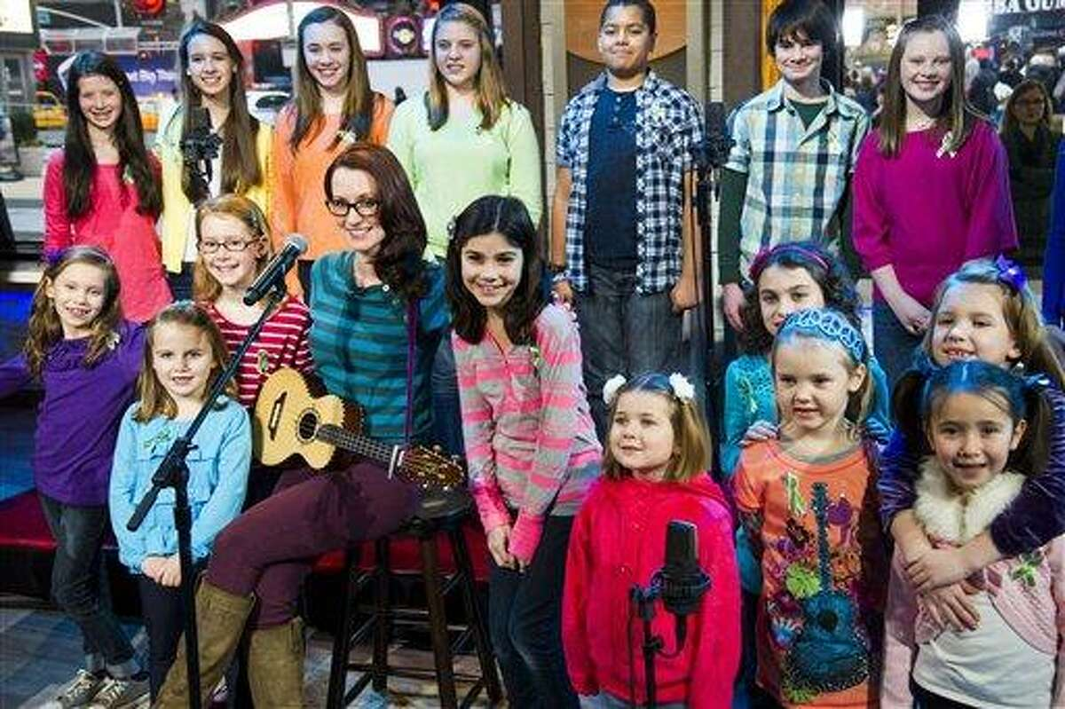 """Ingrid Michaelson accompanied by children from Newtown, Conn. and Sandy Hook Elementary school perform """"Somewhere Over the Rainbow"""" on ABC's """"Good Morning America"""" on Tuesday, Jan. 15, 2013 in New York. The Children who survived last month's shooting rampage, recorded a version of """"Over the Rainbow"""" to raise money for charity. They recorded the song at the home of two former members of the Talking Heads rock band. It went on sale Tuesday on Amazon and iTunes, with proceeds benefiting a local United Way and the Newtown Youth Academy. (Photo by Charles Sykes/Invision/AP)"""