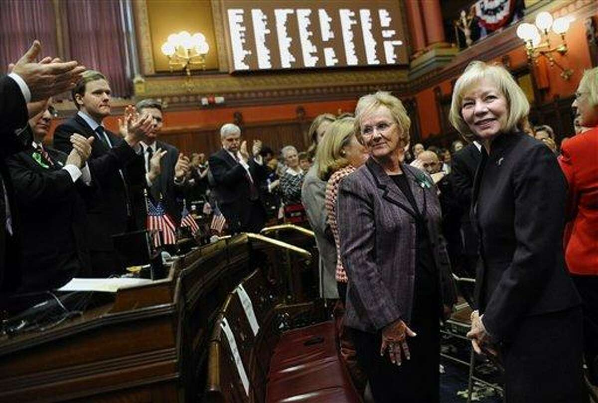 """Newtown First Selectwoman Pat Llodra, center left, and Newtown School Superintendent Dr. Janet Robinson, center right, receive a standing ovation inside the Hall of the House during Gov. Dannel P. Malloy's State of the State address the at the Capitol in Hartford, Conn., Wednesday, Jan. 9, 2013. Malloy urged state lawmakers Wednesday to work with him to prevent future tragedies like the Sandy Hook Elementary School shooting, but stressed that """"more guns are not the answer."""" Legislators also must grapple with a projected deficit of about $1.2 billion. (AP Photo/Jessica Hill)"""