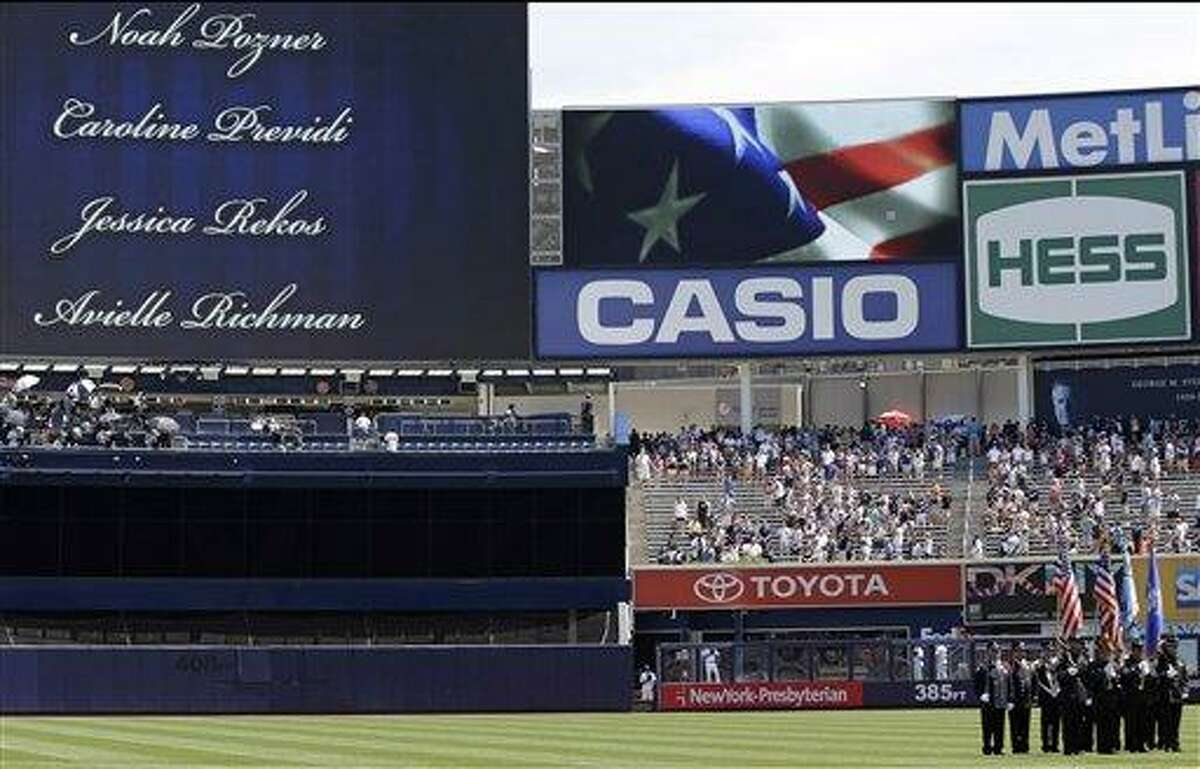 An honor guard of Newtown, Connecticut first responders stands at attention as names of the victims of the Newtown school massacre are shown on a huge video screen in a pregame ceremony prior to the Baltimore Orioles baseball game against the New York Yankees, Sunday, July 7, 2013, at Yankee Stadium in New York. (AP Photo/Kathy Willens)