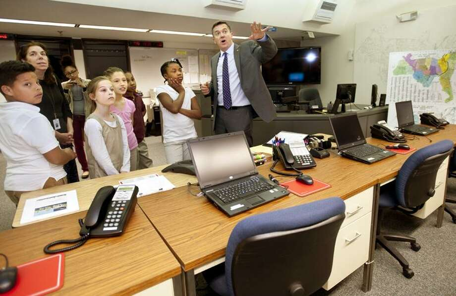 NEWHAVEN-Jim Travers, Director of Transportation, Parking and Traffic, shows a group of 5th graders from Jackie Robinson around the emergency command center at 200 Orange Street.