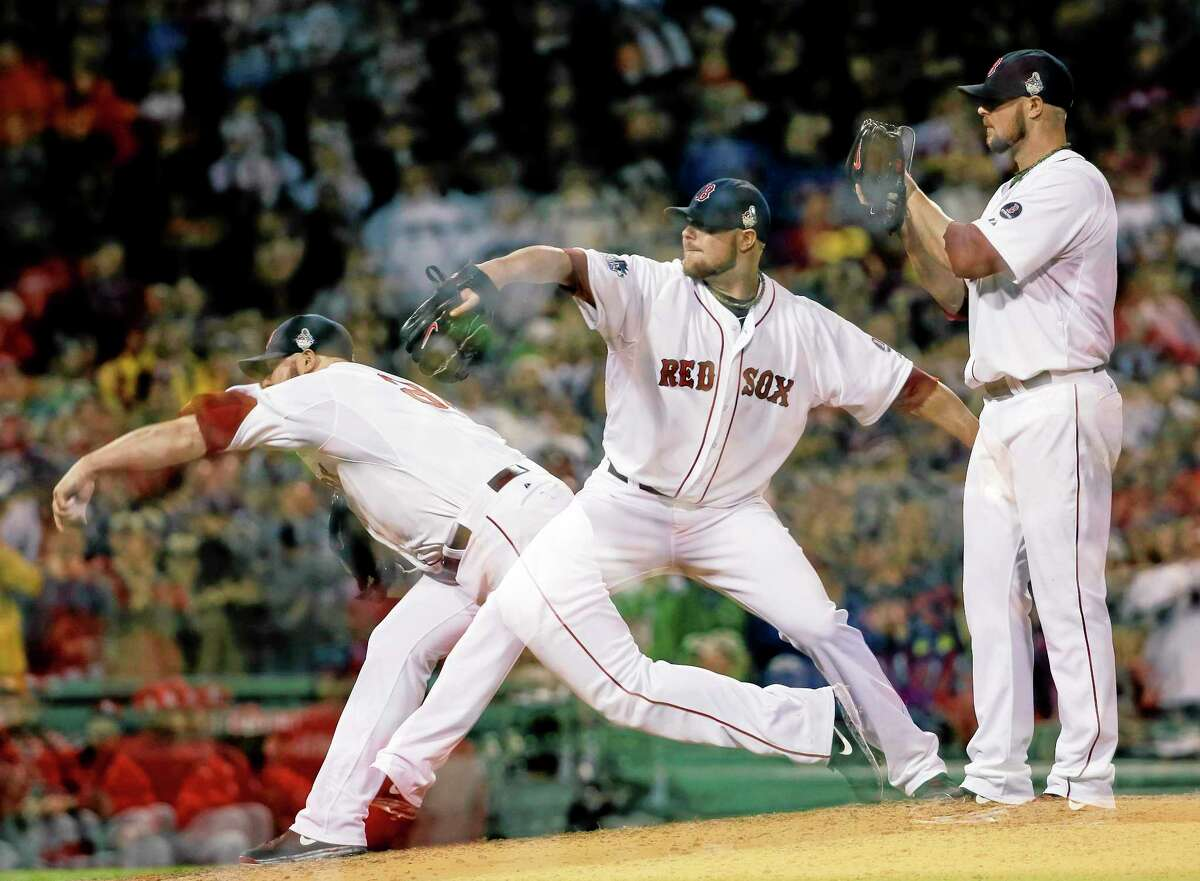 This multiple exposure image shows Red Sox starting pitcher Jon Lester throwing during the seventh inning of Game 1 of the World Series against the St. Louis Cardinals Wednesday at Fenway Park in Boston.
