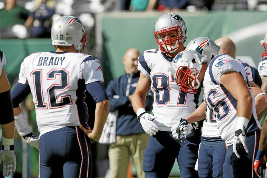 New England tight end Rob Gronkowski (87) talks to teammate Tom Brady before the Patriots' game against the New York Jets on Sunday in East Rutherford. Photo: Seth Wenig — The Associated Press   / AP