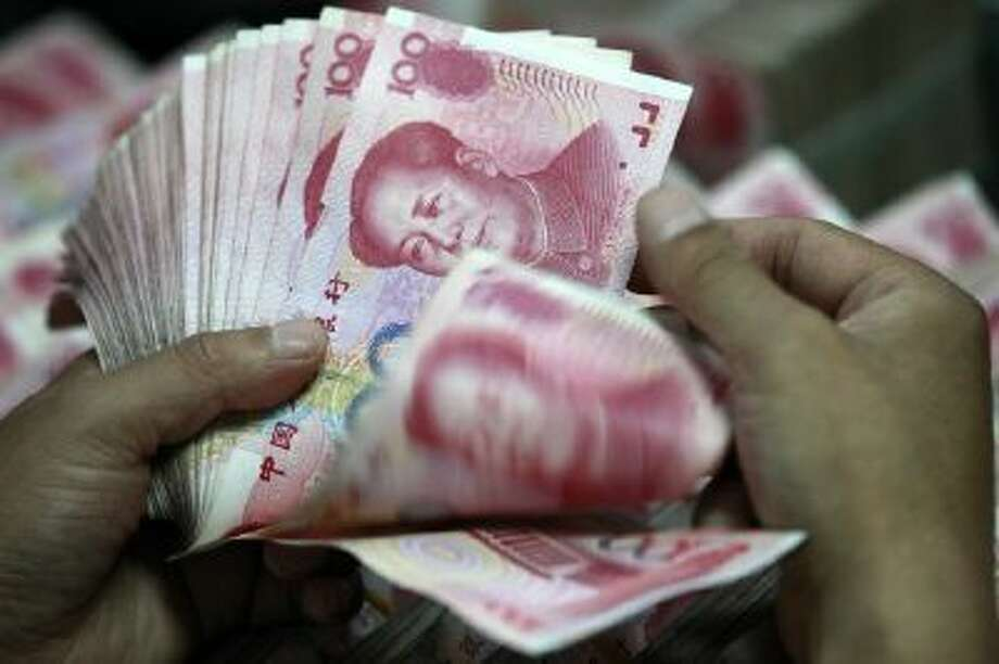A Chinese bank staff member counts stacks of 100-yuan notes at a bank in Huaibei, China, on Aug. 17, 2012.