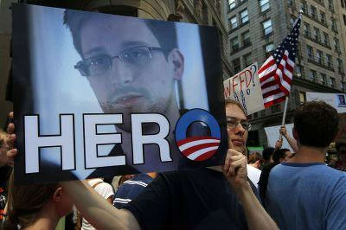 """A demonstrator holds a sign with a photograph of former U.S. spy agency NSA contractor Edward Snowden and the word """"HERO"""" during Fourth of July Independence Day celebrations in Boston, Massachusetts July 4, 2013. (Brian Snyder/Reuters)"""