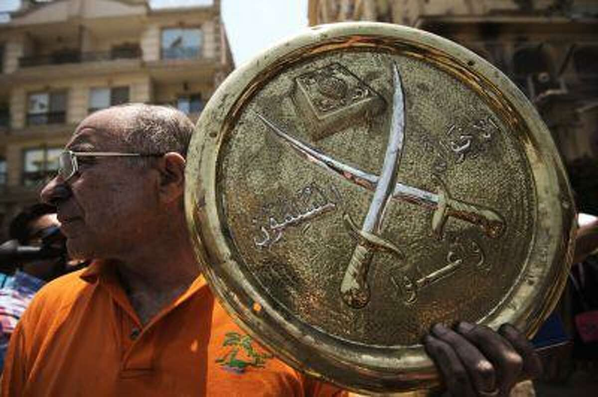 A man holds a plaque of the Muslim Brotherhood emblem which was removed from the party's burnt out headquarters in the Moqattam district of Cairo, on July 1, 2013, after it was set ablaze by opposition demonstrators overnight.