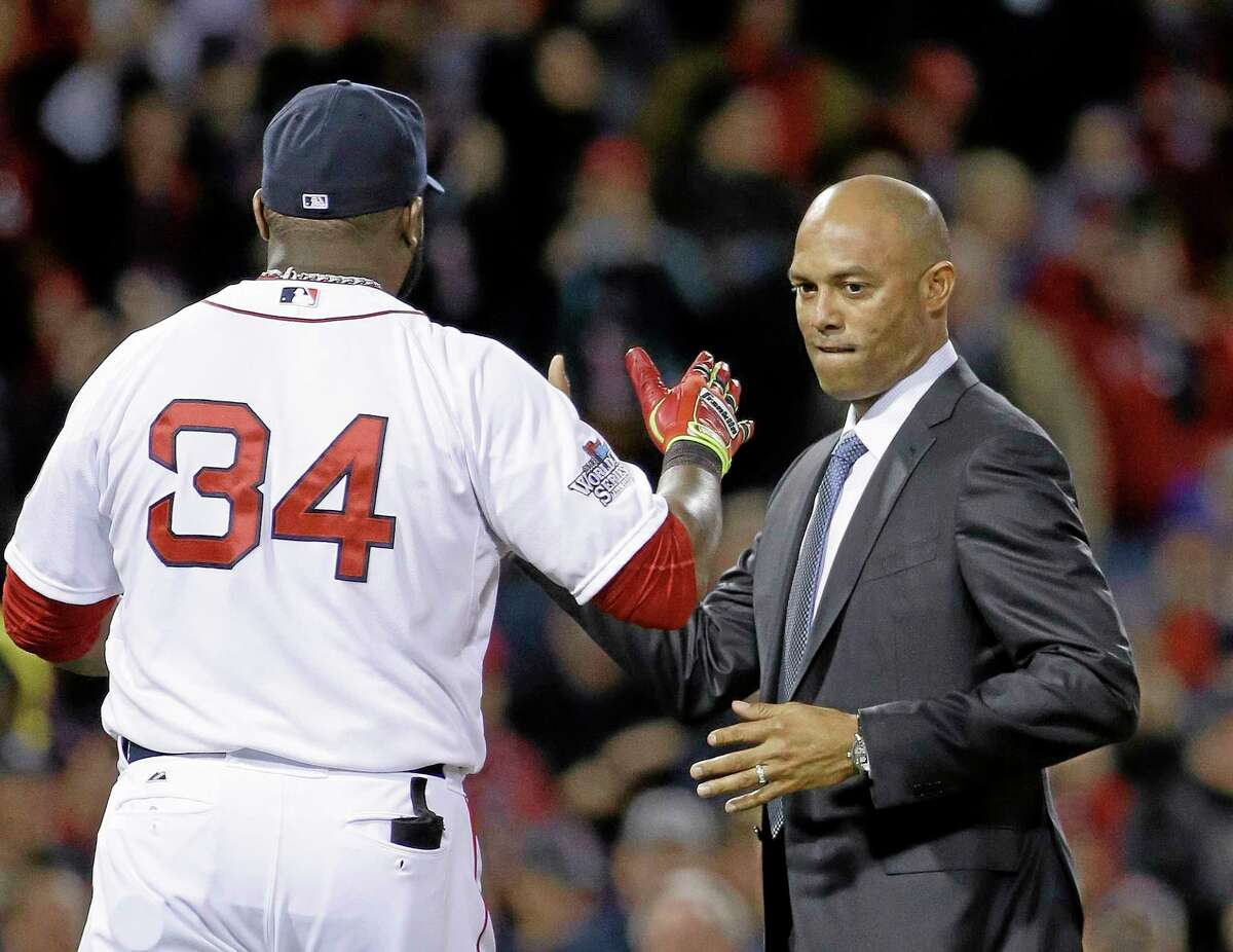 Former New York Yankees closer Mariano Rivera gets a handshake from Boston Red Sox designated hitter David Ortiz before Game 2 of the World Series on Thursday in Boston.