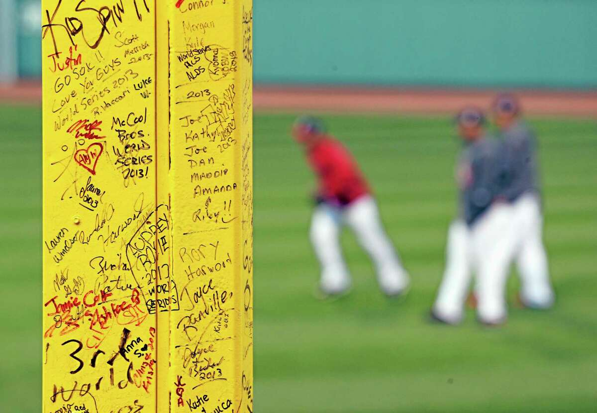 """Fans' signatures are seen on """"Pesky's Pole"""" in right field at Fenway Park as the Boston Red Sox practice before Game 2 of the World Series on Thursday."""