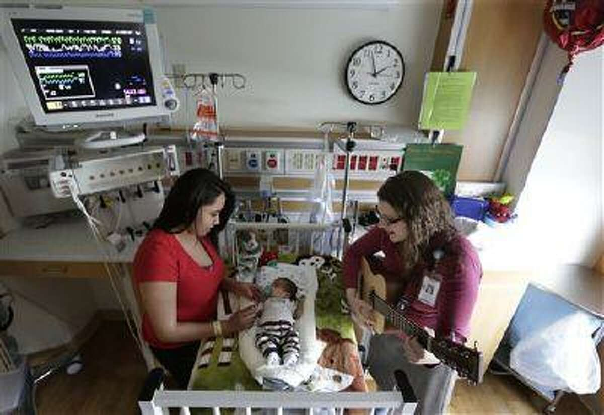 """Music therapist Elizabeth Klinger, right, quietly plays guitar and sings for Augustin as he grips the hand of his mother, Lucy Morales, in the newborn intensive care unit at Ann & Robert H. Lurie Children's Hospital in Chicago on Monday, May 6, 2013. """"The music relaxes him, it makes him feel more calm"""" and helps him sleep better too, Lucy Morales said. """"Sometimes it makes us cry."""""""