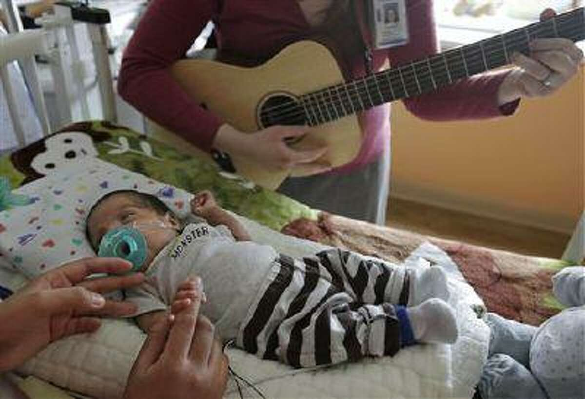 Music therapist Elizabeth Klinger, right, quietly plays guitar and sings for Augustin as he grips the hand of his mother, Lucy Morales, in the newborn intensive care unit at Ann & Robert H. Lurie Children's Hospital in Chicago on Monday, May 6, 2013. Research suggests that music may help those born way too soon adapt to life outside the womb. Recent studies and anecdotal reports suggest the vibrations and soothing rhythms of music, especially performed live in the hospital, might benefit preemies and other sick babies.