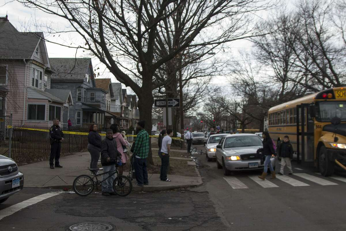 Young students appeared shocked after they were dropped off to a swarm of police cars Monday afternoon at the corner of Howard Avenue and First Street. Police had two people in custody after shots were fired on Columbus Avenue and were searching for additional suspects. Photo by Rich Scinto.