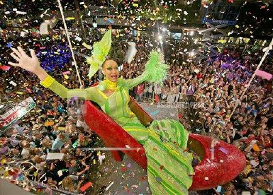 In this photo provided by the Florida Keys News Bureau, Gary Marion, a female impersonator known as Sushi, hangs in an oversized replica of a women's red high heel over Duval Street, late Monday, Dec. 31, 2012, at the Bourbon Street Pub Complex in Key West, Fla. The Red Shoe Drop has become a Key West tradition and is one of five Florida Keys warm-weather takeoffs on New York City's Times Square ball drop marking the beginning of the new year.