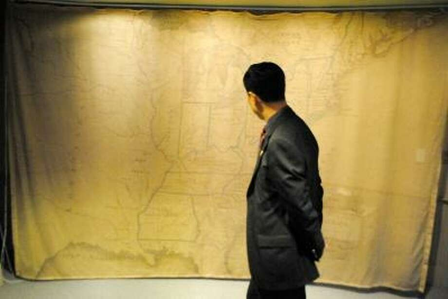 A Chinese judge studies a colonial map of the United States. JESSICA GLENZA/REGISTER CITIZEN.