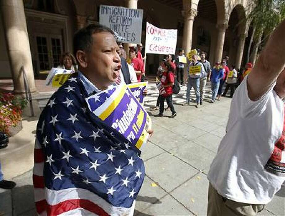 Wearing an American flag, Lino Pedres joined others Oct. 8 in a march to support immigration reform in Sacramento. The U.S. flag often is used during exercises of free speech. Photo: AP / AP