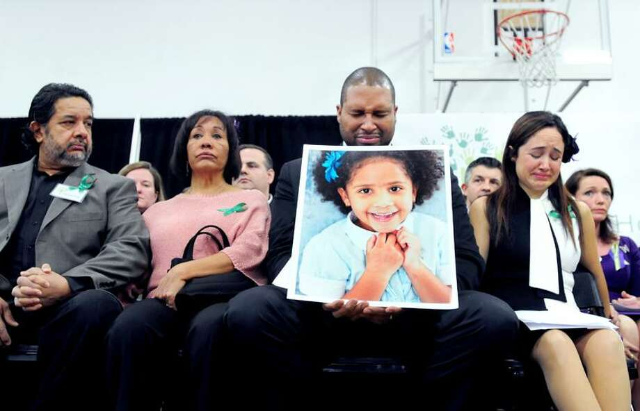 Jimmy Greene holding a photograph of his daughter, Ana Marquez-Greene (who was killed in the Sandy Hook School massacre), and his wife, Nelba Marquez-Greene (right), react during a press conference announcing the launch of Sandy Hook Promise at Edmond Town Hall in Newtown on 1/14/2013.  At left are members of Marquez-Greene's family.Photo by Arnold Gold/New Haven Register