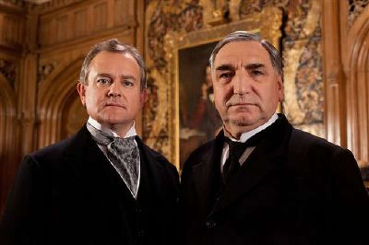 """This undated file publicity image provided by PBS shows Hugh Bonneville as Lord Grantham, left, and Jim Carter as Mr. Carson from the popular series """"Downton Abbey."""" The fourth season of """"Downton Abbey"""" will debut Sunday, Jan 5, 2014."""