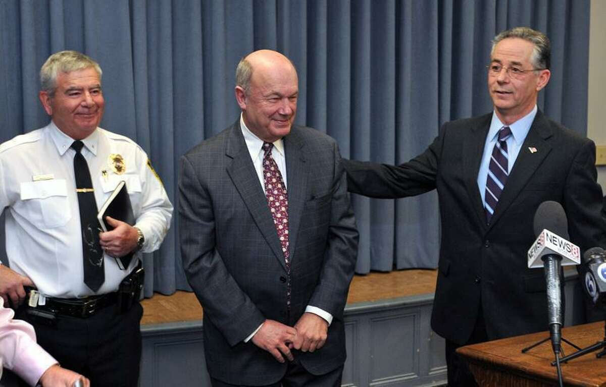East Haven-- Former Stamford police chief Brent Larrabee gets a pat on the back from East Haven Mayor Joe Maturo following a press conference last year. Larrabee was sworn in as East Haven's interim police chief. On the left is Assistant Chief John Mannion. Peter Casolino/New Haven Register 02/14/12