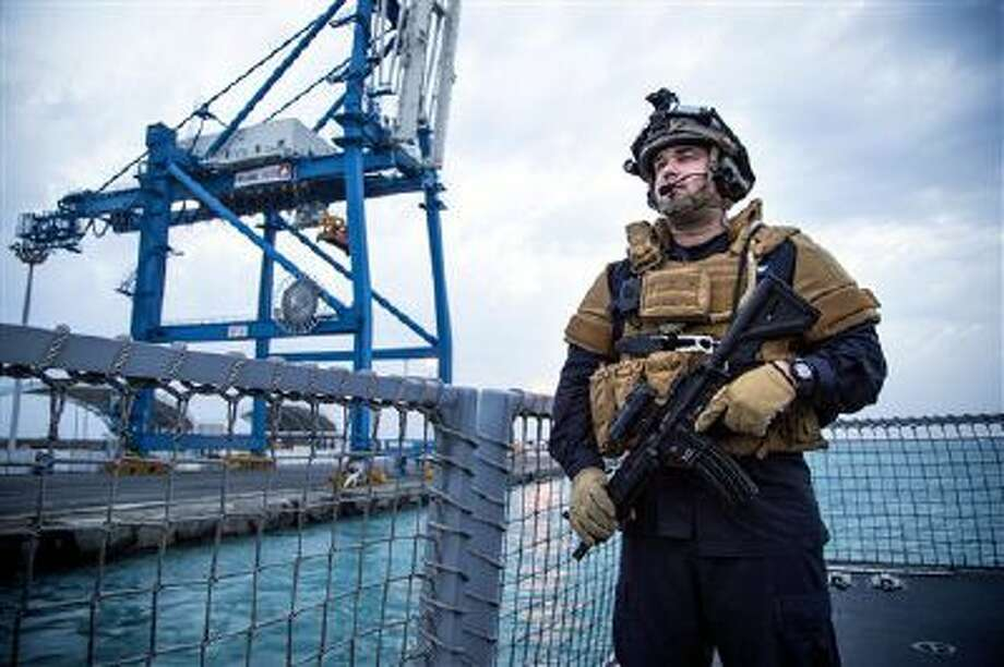 A security forces member stands guard aboard the Norwegian frigate Helge Ingstad, in Limassol, Cyprus. A Danish-Norwegian flotilla is preparing to remove Syria's chemical weapons from the war-torn country by conducting emergency rescue drills. Meanwhile, because of energy investments, Russia has taken on new interest in the region, including Cyprus. (AP Photo/Norwegian Armed Forces, Lars Magne Hovtun) Photo: AP / Norwegian Armed Forces