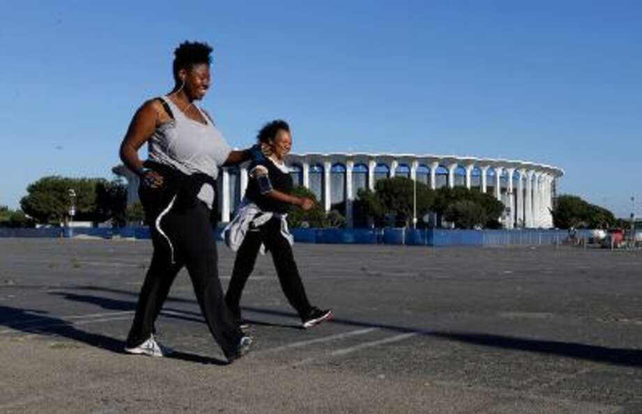 People walk, jog and run on the parking lot and grounds of The Forum, where the likes of Elvis Presley and the Rolling Stones played to thousands of screaming fans, in Inglewood, Calif.