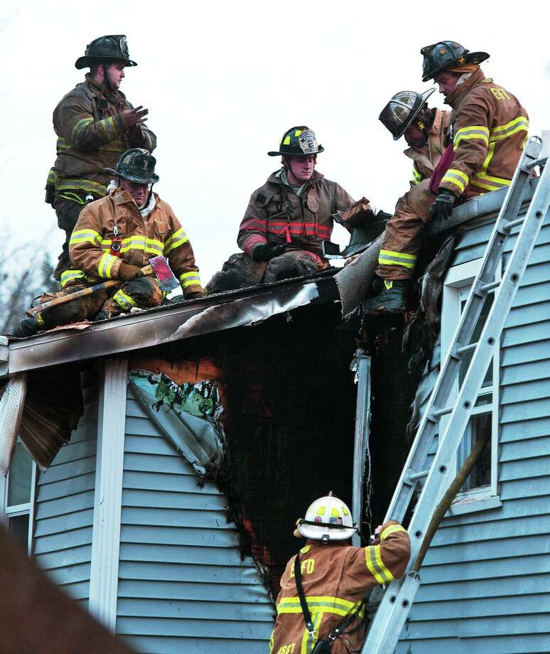 East Haven firefighters look for the cause of a blaze at the house at 937 North High St. late Monday afternoon. Photo: Peter Casolino — New Haven Register