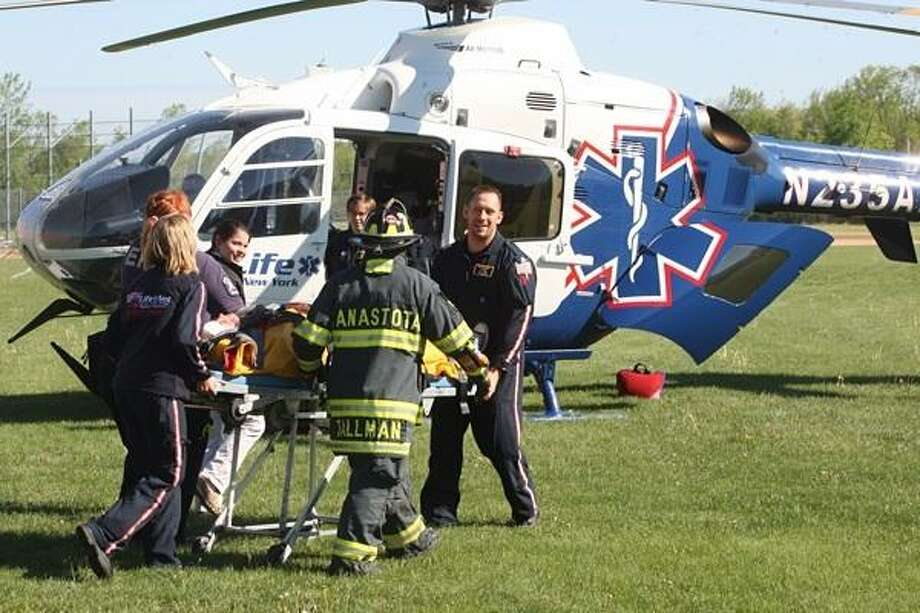 PHOTO BY JOHN HAEGER @ ONEIDAPHOTO ON TWITTER/ONEIDA DAILY DISPATCH Rescue crews prepare to transport a victim by helicopter    during a mock DWI accident at Canastota High School on Thursday, May 16, 2013.