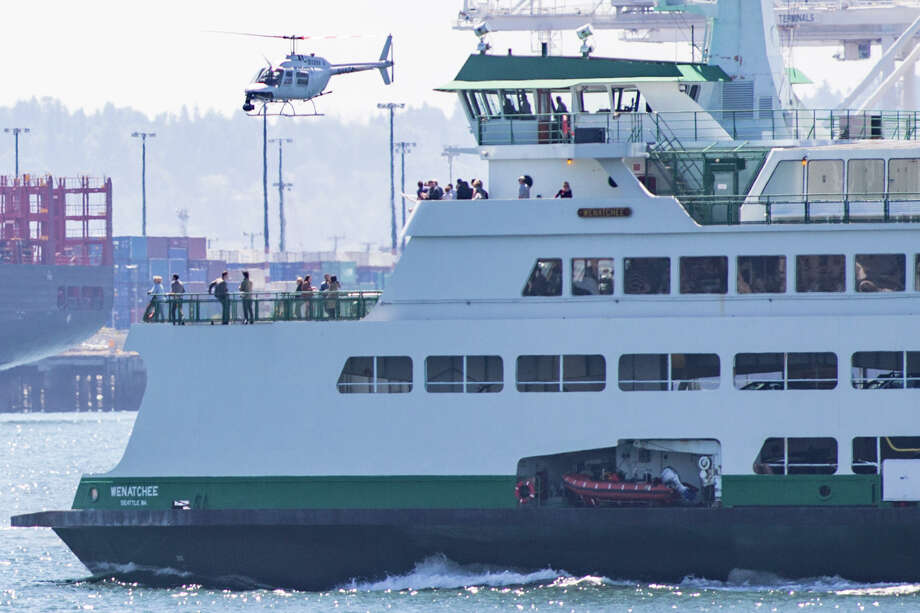 A filming helicopter follows the Seattle-Bainbridge ferry for the next season of Grey's Anatomy, Tuesday, July 25, 2017. Photo: GRANT HINDSLEY, SEATTLEPI.COM / SEATTLEPI.COM