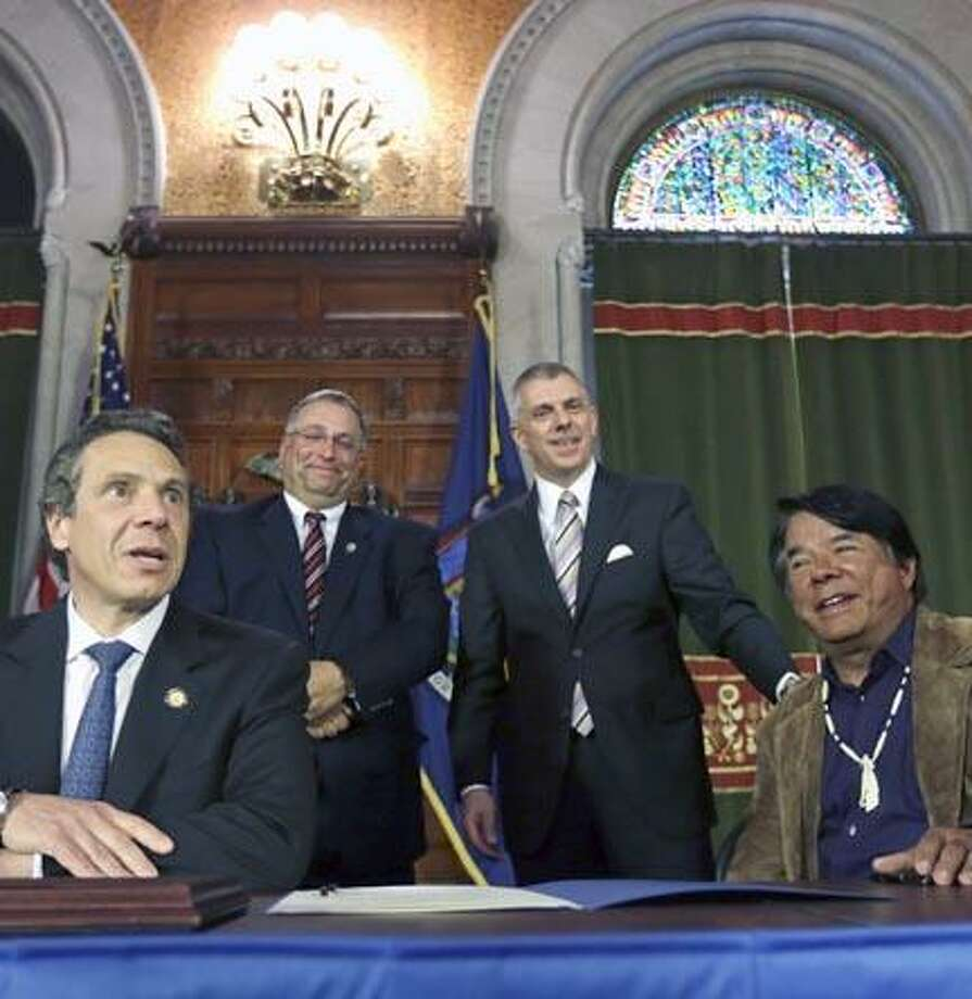 From left, New York Gov. Andrew Cuomo, Madison County Board of Supervisors Chairman John Becker, Oneida County Executive Anthony Picente and Ray Halbritter of the Oneida Indian Nation pose after a news conference on Thursday, May 16, 2013, in Albany, N.Y. The tribe has struck a deal with the Cuomo administration to guarantee exclusive territory for their casino in exchange for an estimated $50 million in annual payments to the state, plus payments to the counties and an end to all current litigation. (AP Photo/Mike Groll) Photo: AP / AP
