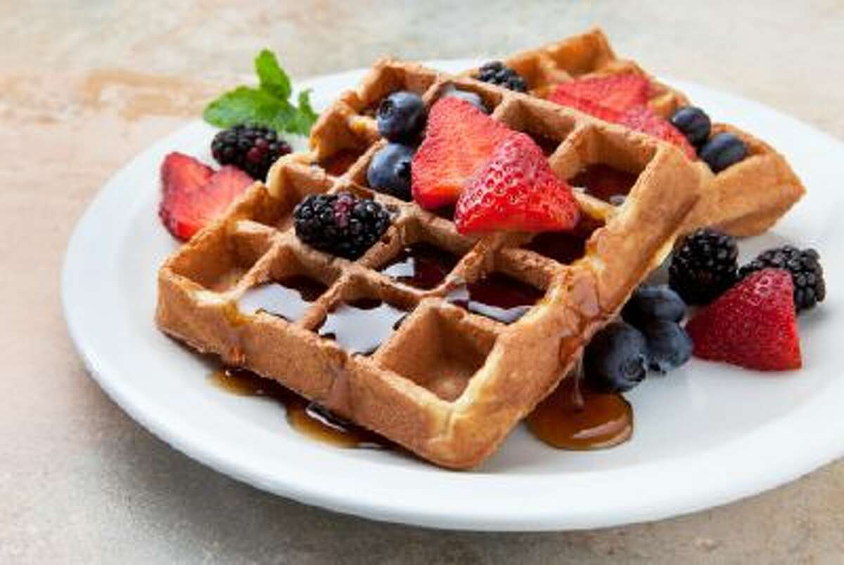 A plate of belgian waffles with fruit on a marble counter.