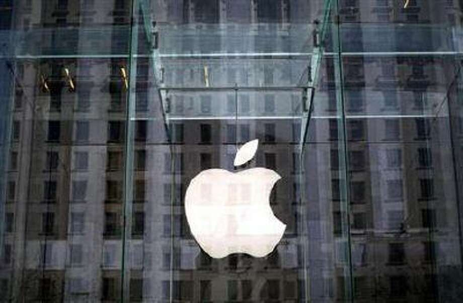 The Apple logo hangs inside the glass entrance to the Apple Store on 5th Avenue in New York City, April 4, 2013. (Credit: Reuters/Mike Segar)