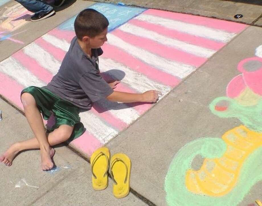 JOHN HAEGER @ONEIDAPHOTO ON TWITTER/ONEIDA DAILY DISPATCH Gavin Marsh ,9, of Binghamton NY adds the final touches to his drawing of an American Flag during the annual Chalk the Walk in Sylvan Beach on Saturday, July 6, 2013.