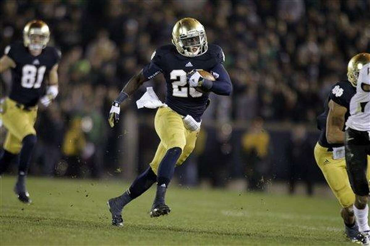 Notre Dame running back Cierre Wood (20) cuts around Wake Forest defenders as he picks up 42 yards during the second half of an NCAA college football game in South Bend, Ind., Saturday, Nov. 17, 2012. Notre Dame defeated Wake Forest 38-0. (AP Photo/Michael Conroy)