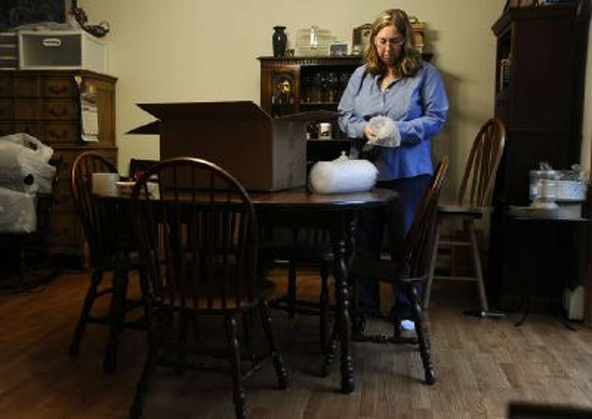 In this Dec. 23, 2013 photo, Leslie Lynch packs up belongings in her dining room in Glastonbury, Conn. Lynch who lost her job last year is moving out of her home of 21 years because she can no longer afford the mortgage payments.