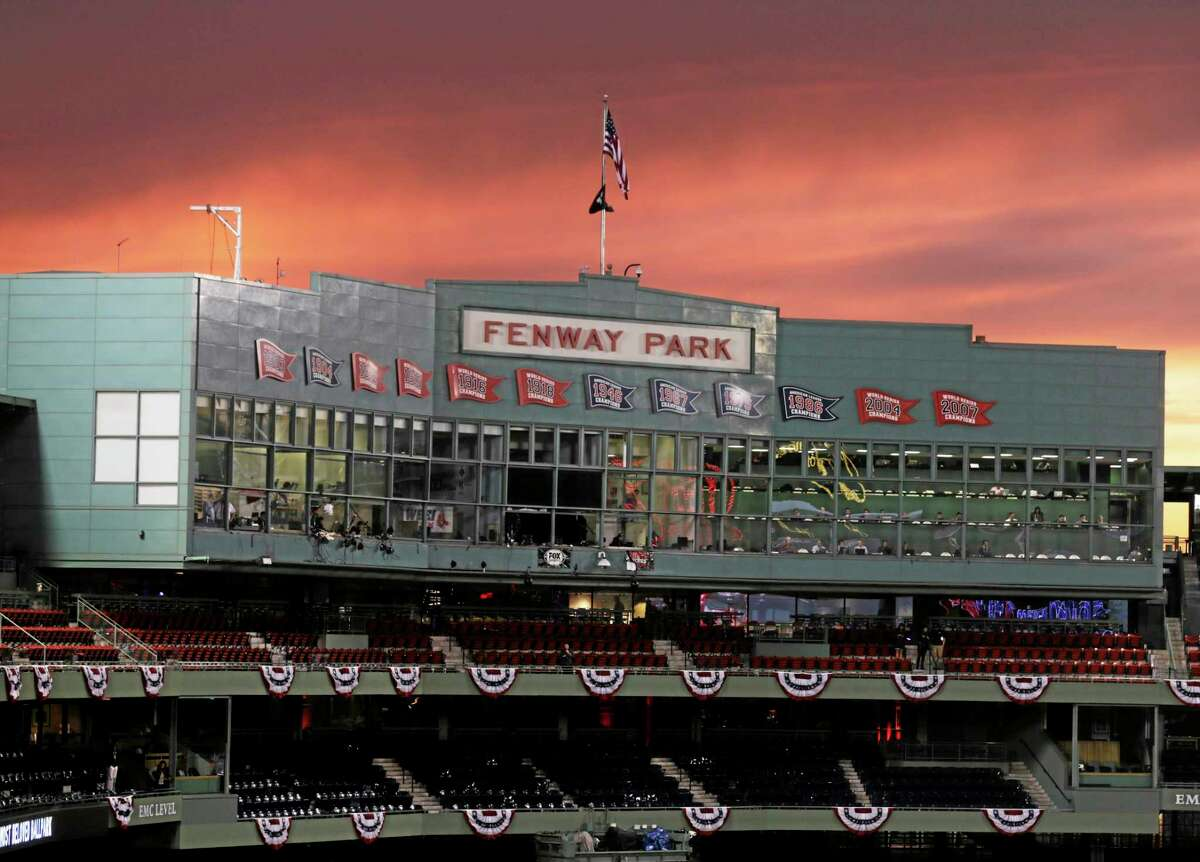 The sun sets over Fenway Park as the Boston Red Sox work out Tuesday in Boston. The Red Sox will host the St. Louis Cardinals in Game 1 of the World Series on Wednesday.