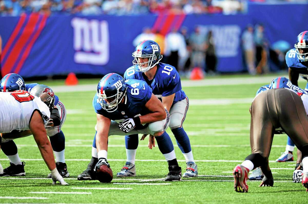 Giants quarterback Eli Manning prepares to take the snap from center David Baas during a 2012 game.