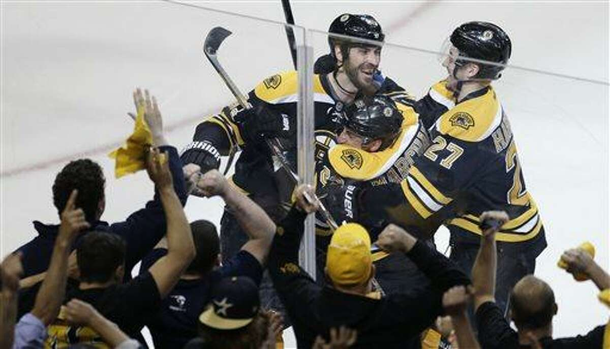 Boston Bruins left wing Brad Marchand, center, is congratulated by teammates Dougie Hamilton (27) and Zdeno Chara, left, following his game-winning goal against New York Rangers goalie Henrik Lundqvist during overtime in Game 1 of an NHL hockey playoffs Eastern Conference semifinal game in Boston, Thursday, May 16, 2013. The Bruins won 3-2. (AP Photo/Charles Krupa)