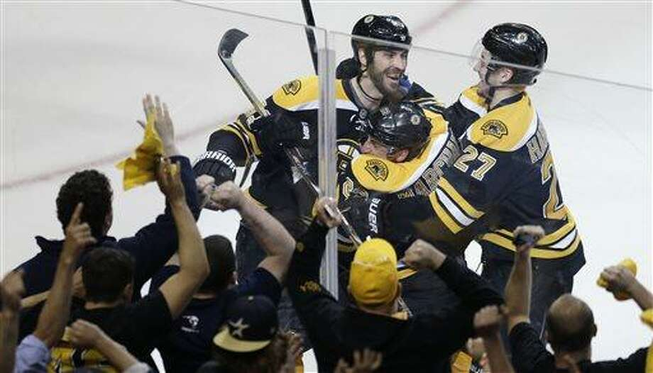 Boston Bruins left wing Brad Marchand, center, is congratulated by teammates Dougie Hamilton (27) and Zdeno Chara, left, following his game-winning goal against New York Rangers goalie Henrik Lundqvist during overtime in Game 1 of an NHL hockey playoffs Eastern Conference semifinal game in Boston, Thursday, May 16, 2013. The Bruins won 3-2. (AP Photo/Charles Krupa) Photo: AP / AP
