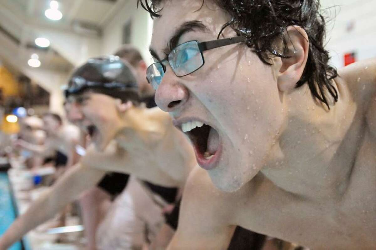 Catherine Avalone/The Middletown Press Haddam-Killingworth senior captain Neal Tyson and junior Mike Szafran cheer on their teammate Garrett Mazziotti who finishes up the final leg in the 200 freestyle relay in the CIAC Class S Swim Championship at Wesleyan's Freeman Athletic Center. Tyson, Conor Champagne, Szafran and Mazziotti placed first with a time of 1:32.25.