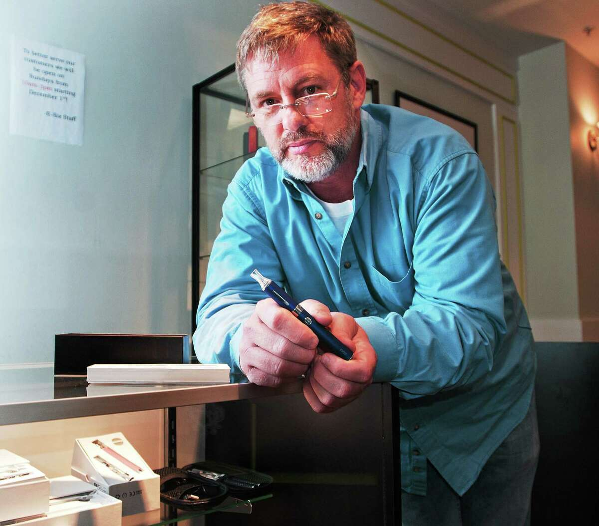 (Peter Casolino ó New Haven Register) Ted Szabo, one of the owners of E-Six, electronic cigarette retailer in Branford, holds a eVod, the store's most popular e-cigarette kits. pcasolino@NewHavenRegister