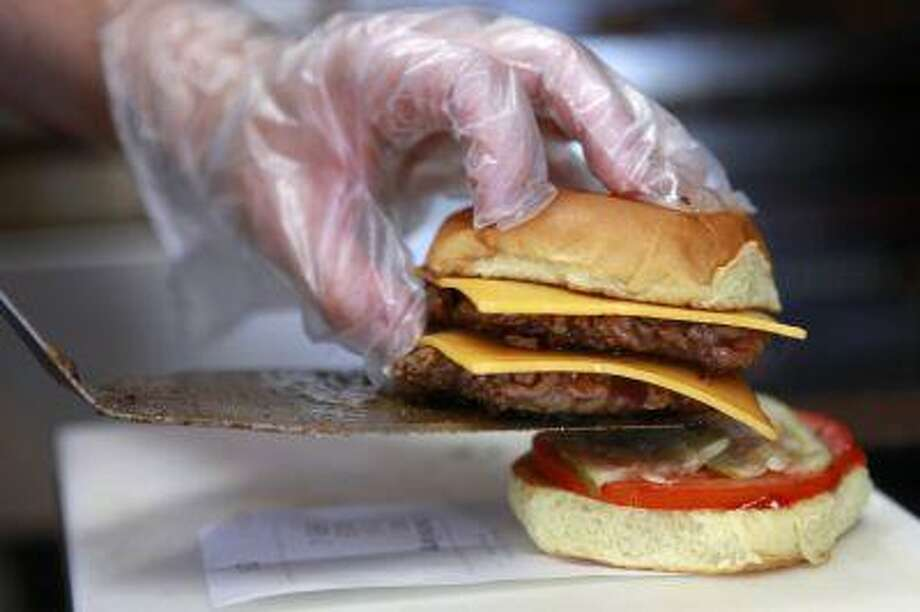 There's a burger war brewing in Britain. American chains Five Guys and Shake Shack are opening their doors across the pond for the first time. In this photo, April Hess prepares a hamburger at Elevation Burger in Potomac, Md. (AP Photo/Jacquelyn Martin) Photo: ASSOCIATED PRESS / AP2010