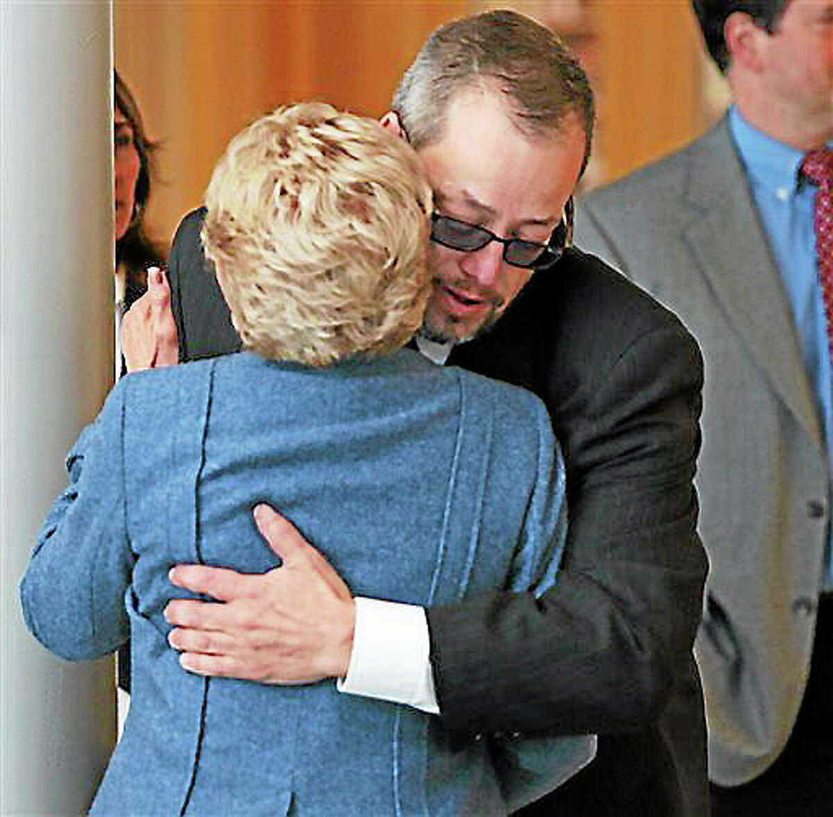 Gardner Trask, chairman of the Danvers Board of Selectman, embraces an unidentified woman inside Danvers High School prior to a press conference by Jonathan Blodget, Essex District Attorney, Wednesday, Oct. 23, 2013 where he announced the homicide death of Danvers math teacher Colleen Ritzer at Danvers High School in Danvers, Mass. A 14-year-old Massachusetts high school student is facing a murder charge in the death of the teacher found dead in the woods behind the school. (AP Photo/Boston Herald, Mark Garfinkel) BOSTON GLOBE OUT; METRO BOSTON OUT; MAGS OUT; ONLINE OUT NO SALES
