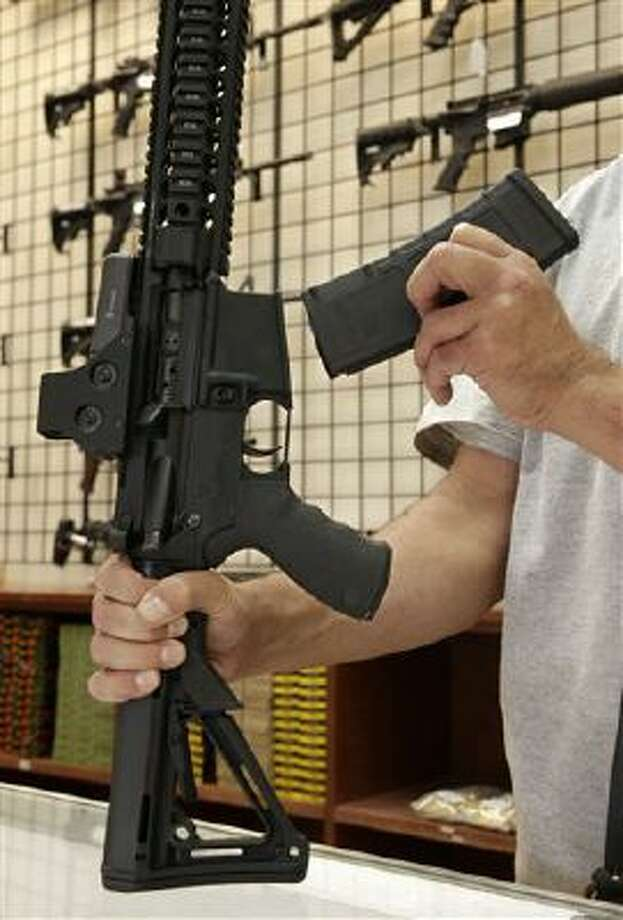 A custom made semi-automatic hunting rifle with a detachable magazine is displayed at a gun store in California. (AP Photo/Rich Pedroncelli) Photo: AP / AP