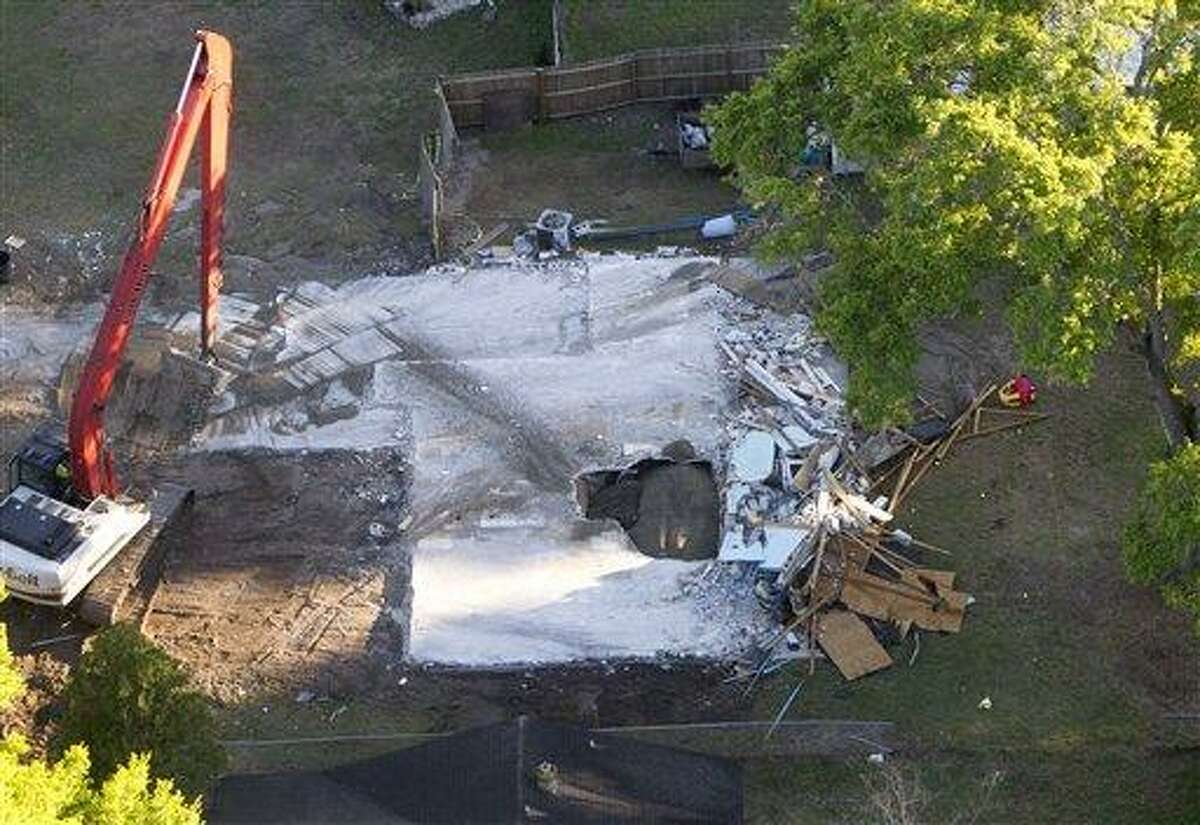 This Aerial photo shows the giant sinkhole at the home of Jeff Bush, Tuesday, March 5, 2013, in Seffner, Fla. A huge sinkhole opened up under a bedroom in the home last Thursday, Feb. 28, and swallowed Jeff Bush, 37. Officials gave up hope of finding Bush alive and filled in the hole with crushed rock. (AP Photo/The Tampa Bay Times, Dirk Shadd)